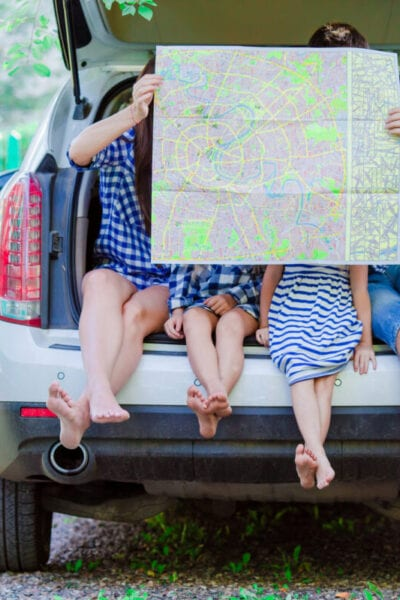 Family with two kids looking at map while traveling by car