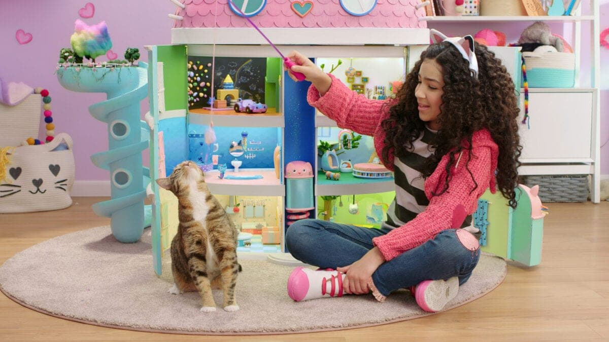 Gabby from Gabby's Dollhouse playing with her cat